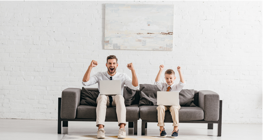 Man and boy sitting on couch working on laptops with arms raised