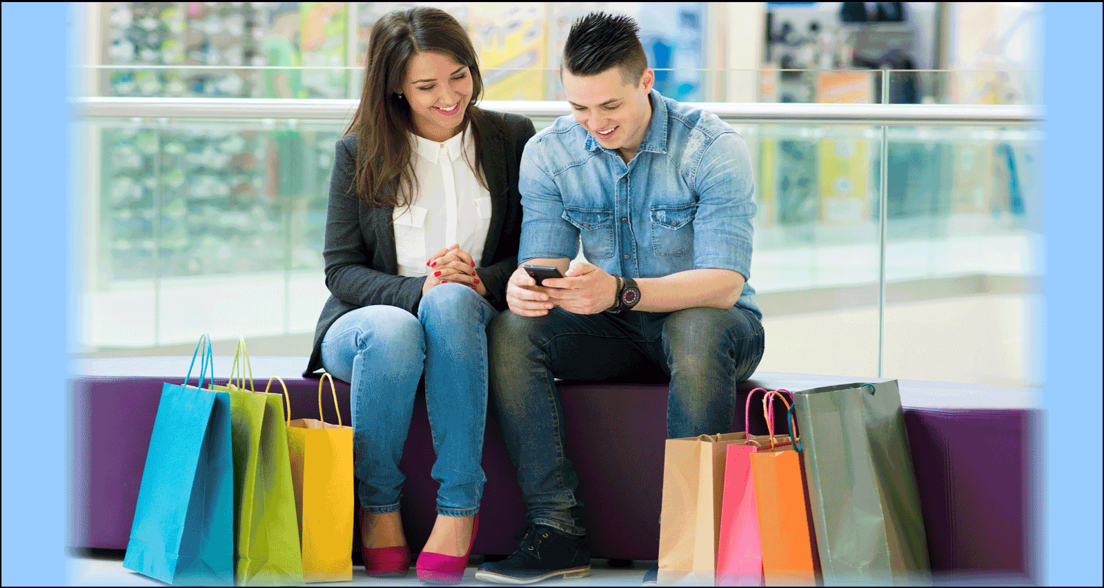 couple looking at phone with shopping bags on ground